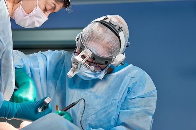 Das team der chirurgen führt eine invasive operation durch. porträt von chirurgen nahaufnahme. arbeiten sie mit einem gerinnungsinstrument, der gefäßgerinnung