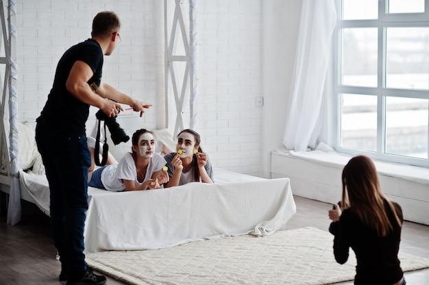 Das team von zwei fotografen, die auf studio-zwillingsmädchen schießen, während sie ihre eigenen crememasken herstellen. professioneller fotograf bei der arbeit.