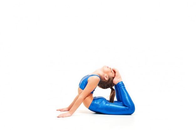 Das teenager-mädchen, das gymnastikübungen lokalisiert auf weißer wand tut