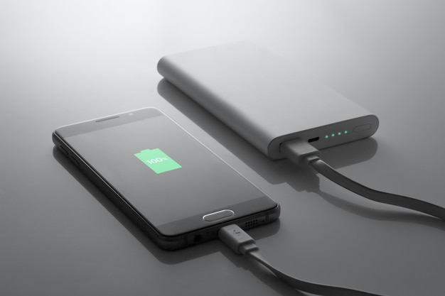 Das telefon wird von der powerbank in dunklen tönen zu 100% aufgeladen