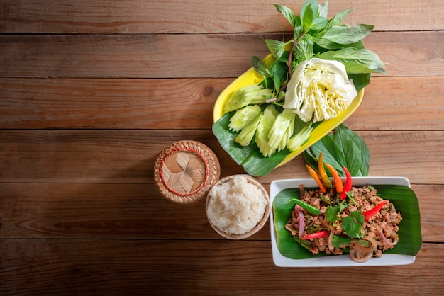 Das thailändische lebensmittel, das laab moo genannt wird, essen mit klebrigem reis im klebrigen reis kratib