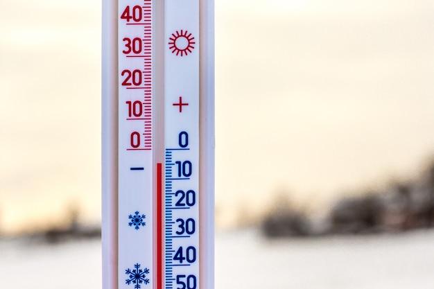 Das thermometer auf einem hintergrund der winterlandschaft bei sonnenuntergang zeigt grad