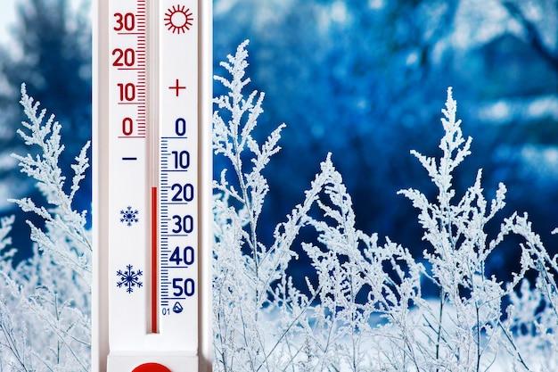 Das thermometer auf einem hintergrund der winterlandschaft