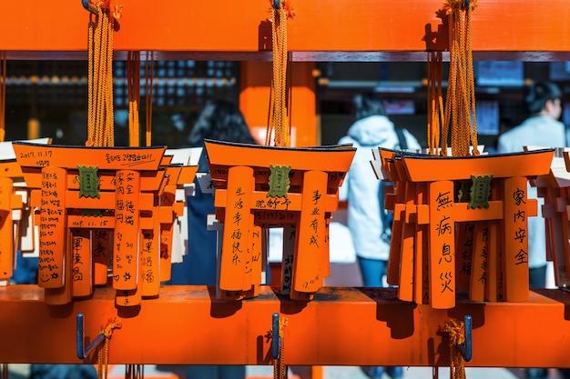 Das torii-tor-modell hing am gestell, nachdem der tourist es benutzt hatte, um sich im fushimi inari-schrein in kyoto etwas zu wünschen.