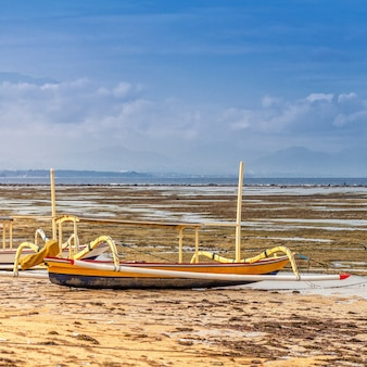 Das traditionelle balinesische fischerboot steht bei ebbe an der küste des ozeans und an der küste.