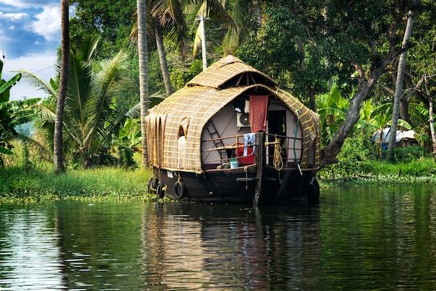 Das traditionelle hausboot liegt an den ufern eines fischteichs in indien.