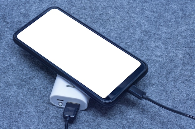 Das tragbare ladegerät lädt ein smartphone auf grauem hintergrund auf. handy-modell mit weißem bildschirm und power bank.