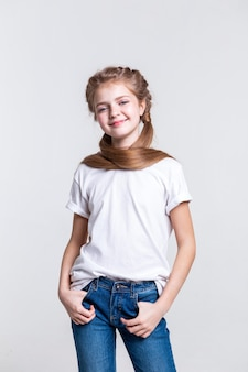 Das tragen eines gewöhnlichen outfits. angenehmes hübsches mädchen mit gesunden langen haaren, das glücklich ist, während es für die kamera posiert und lächelt