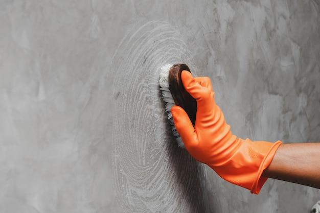 Das tragen von orangefarbenen gummihandschuhen wird verwendet, um die reinigung von schrubben an der betonwand zu ändern.