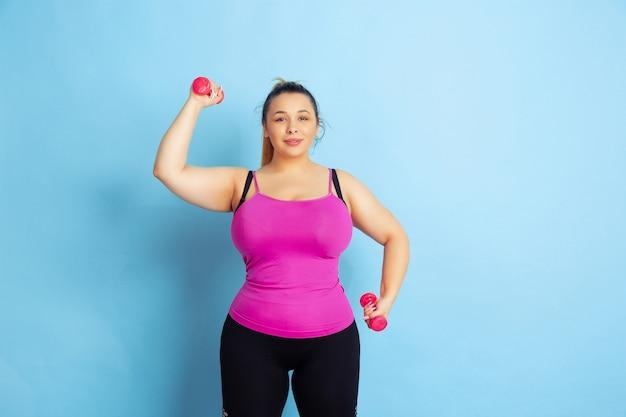 Das training des jungen kaukasischen übergrößen-weiblichen modells auf blauem raum