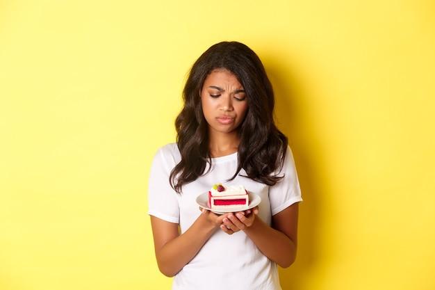 Das traurige afroamerikanische mädchen, das ein stück kuchen betrachtet, kann es nicht essen, wenn es auf diät ist