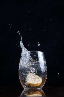 Das trinken der bewegung von kohlensäurehaltigem wasser lässt zitronen-zitrusfrüchte in ein klares glas fallen und spritzt unscharfen hintergrund
