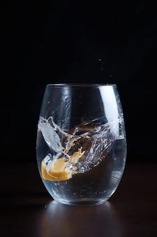 Das trinken von kohlensäurehaltigem wasser lässt zitronen-zitrusfrüchte in ein klares glas fallen und spritzt verschwommen