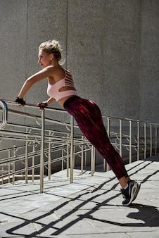 Das üben der jungen frau drückt ups in einen park. seitenansicht geschossen vom muskulösen weiblichen trainieren