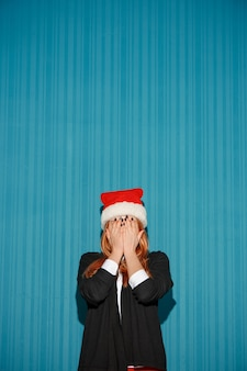 Das überraschte weihnachtsmädchen, das eine weihnachtsmütze auf dem blauen hintergrund trägt