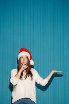 Das überraschte weihnachtsmädchen, das eine weihnachtsmütze trägt, zeigt rechts auf dem blauen hintergrund