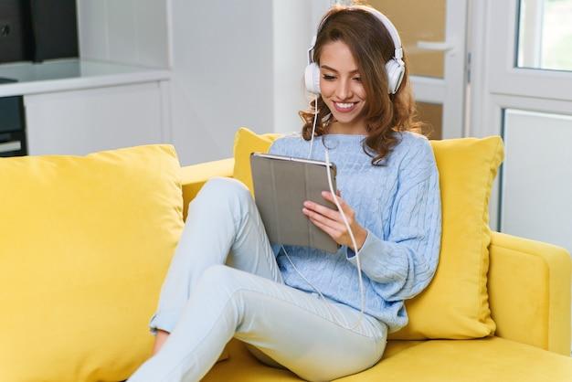 Das überschwängliche mädchen im alter von 30 jahren mit welligem braunem haar und weißen kopfhörern hört musik und benutzt einen laptop oder ein tablet, um sich auf der gelben couch in einem gemütlichen zuhause auszuruhen.