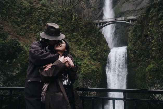 Das umarmen des asiatischen paares steht vor einem schönen wasserfall in den bergen