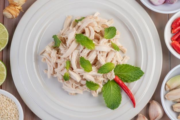 Das umrandete huhn wird gekocht und zusammen mit minzblättern auf einen weißen teller gelegt.