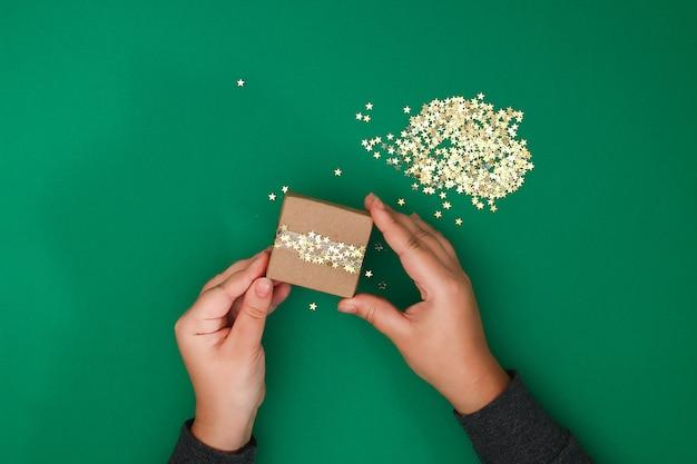 Das ursprüngliche design eines weihnachtsgeschenks aus kraftpapier, scotch und konfetti aus goldsternen