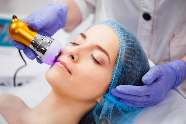 Das verfahren der photoepilation im schönheitssalon. einer jungen frau werden unerwünschte haare im gesicht entfernt. hardware-kosmetologie. mikrostromtherapie. nahansicht