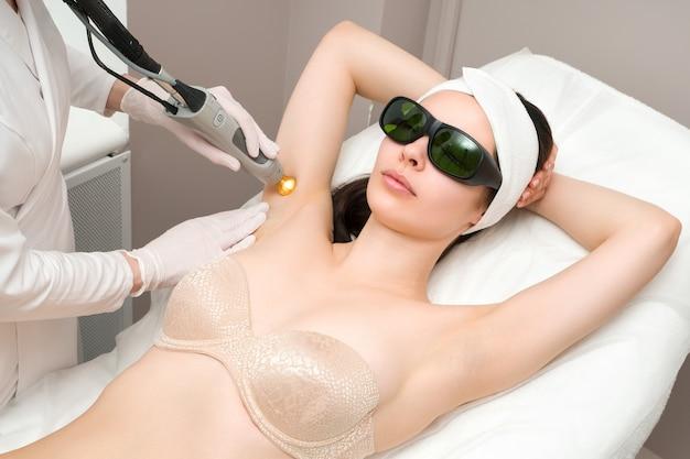 Das verfahren zum entfernen von haaren am körper einer frau in einer kosmetikklinik laser-haarentfernung