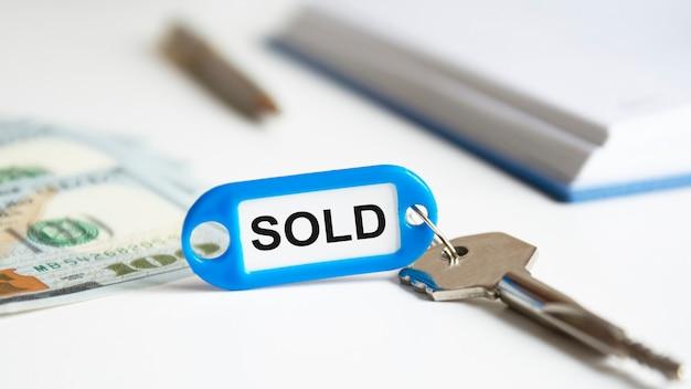 Das verkaufte wort wird auf ein blaues keychain geschrieben. der schlüssel liegt auf dem schreibtisch. im hintergrund hält eine frauenhand geldscheine