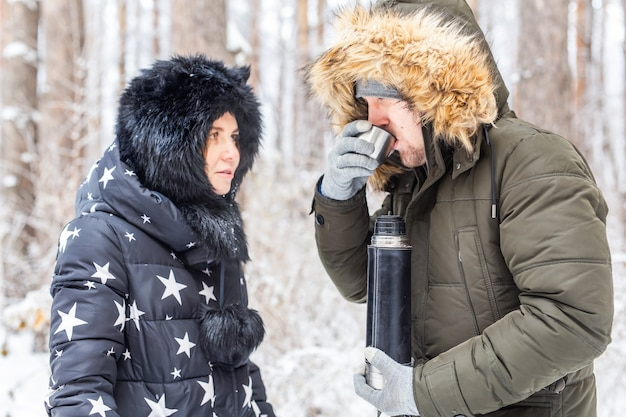 Das verliebte junge paar trinkt ein heißes getränk aus einer thermoskanne und genießt die winternatur.