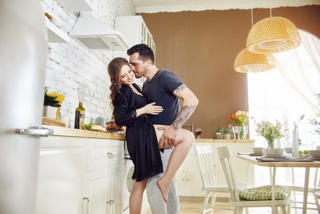 Das verliebte paar in der küche umarmt sich morgens und bereitet das frühstück zu. glückliches familienleben. freude und lächeln im gesicht von männern und frauen
