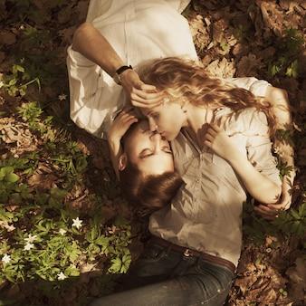 Das verliebte paar liegt im park im gras