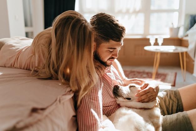 Das verliebte paar schaut auf labrador, der liegt und schläft. mann und frau entspannen sich in gemütlicher atmosphäre.