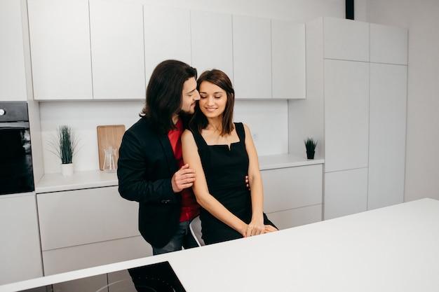 Das verliebte paar umarmt sich zärtlich in einer gemütlichen häuslichen umgebung in der küche