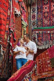 Das verliebte paar wählt einen türkischen teppich auf dem markt.