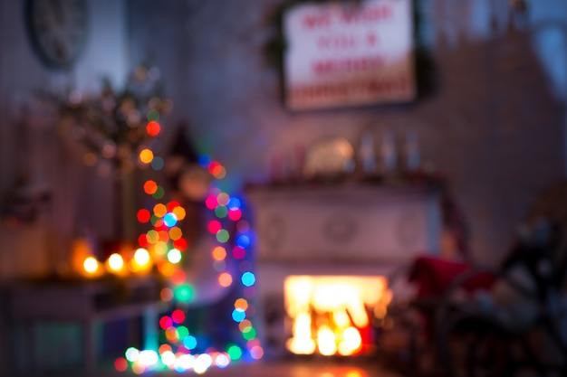 Das verschwommene weihnachts- und neujahrsinterieur des wohnzimmers. alter schaukelstuhl am geschmückten baum- und kaminraum.