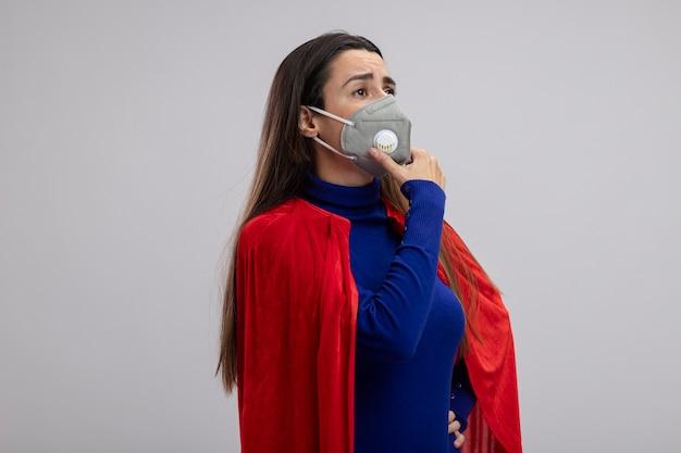 Das verspielte junge superheldenmädchen, das die seite mit der medizinischen maske betrachtet, packte das kinn isoliert auf weiß