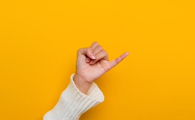 Das versprechen eines kleinen fingers einer weißen asiatischen frau, der auf gelben hintergrundgesten gespalten ist