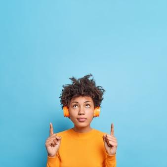 Das vertikale bild einer ernsthaften, schönen afroamerikanischen frau, die oben konzentriert ist, zeigt nach oben, dass kopienraum für ihren werbeinhalt angezeigt wird oder das logo musik über kopfhörer hört. platzieren sie ihren text hier