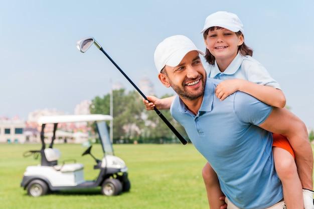 Das war ein gutes spiel. fröhlicher junger mann, der seinen sohn huckepack trägt, während er auf dem golfplatz steht