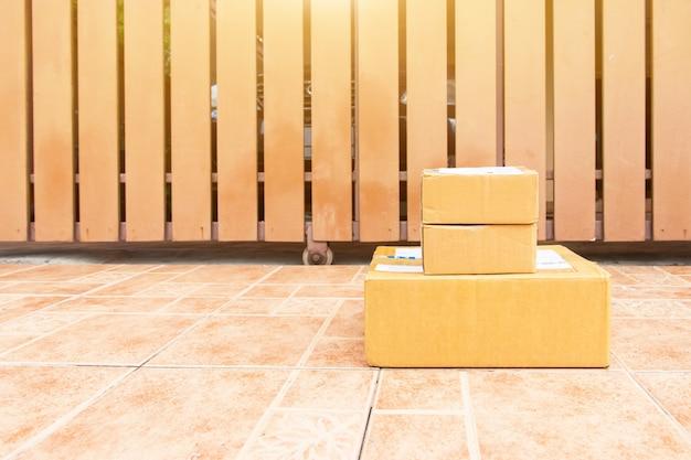 Das warenpaket und an den empfänger zu hause gesendet, lieferbote hält kisten person, die die paketbox an den empfänger gesendet hat, um zu hause anzukommen
