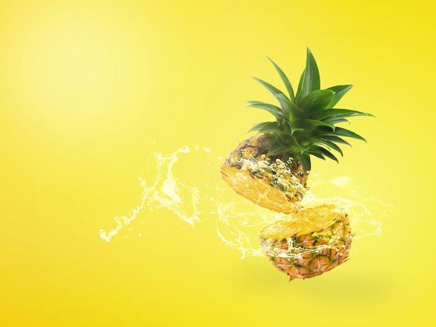 Das wasser, das auf frischer ananas spritzt, ist die tropische frucht, die auf gelbem hintergrund lokalisiert wird.