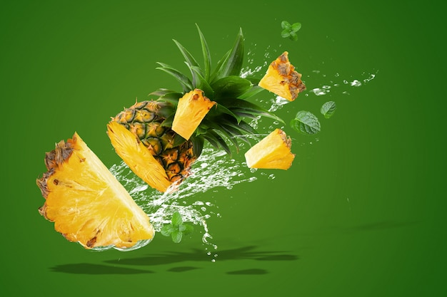 Das wasser, das auf frischer ananas spritzt, ist die tropische frucht, die auf grün lokalisiert wird