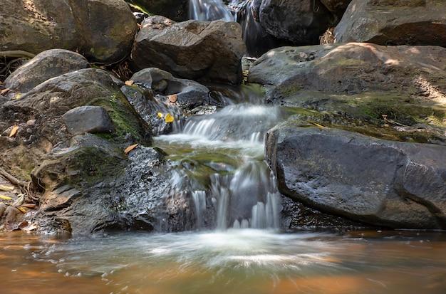Das wasser, das über felsen und bäume hinunter einen wasserfall an wasserfall khao ito, prachin buri in thailand fließt.