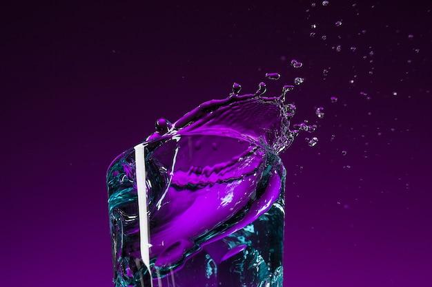 Das wasser spritzt im glas auf lila hintergrund im studio. lebendige helle farbige beleuchtung. trendige 2018 ultra violet glühbirne. kunstdekoration mit mystischem farbton