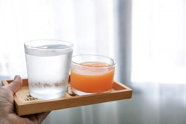 Das wasser und der orangensaft werden in ein holztablett gegeben, das zum trinken geeignet ist, um den körper zu erfrischen und zu heilen.