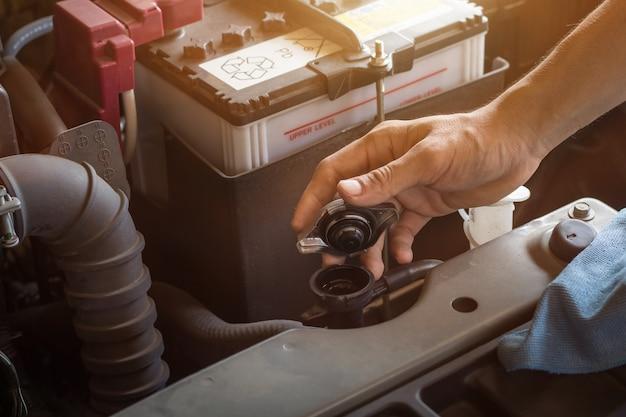 Das wasser und die batterie des automechaniker-arbeitskontrollsystems füllen einen alten automotor an der tankstelle, wechseln und reparieren ihn vor der fahrt