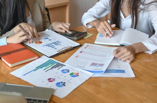 Das weibliche büropersonal-team fasst das budget für die jährliche präsentation der geschäftsleitung zusammen.