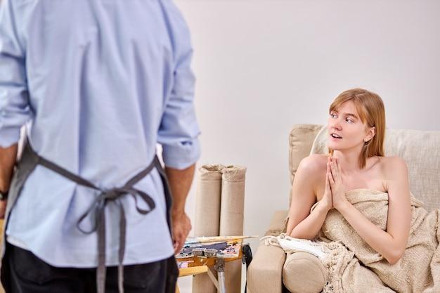 Das weibliche modell betrachtet überraschenderweise zeichnung, kunst. rückansicht auf professionellen künstler, der porträt der frau zeigt, im studio