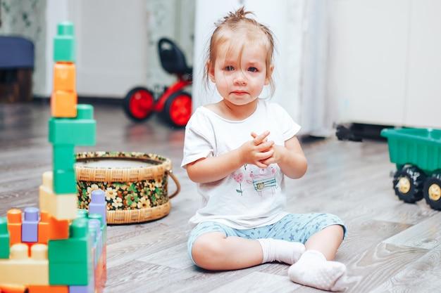 Das weinende kleine mädchen, das auf fußboden sitzt, ist sie verärgert