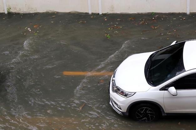Das weiße auto fährt durch überflutete straßen. weicher fokus. transport- und umweltkonzept.