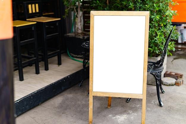 Das weiße, leere blatt wird vor einem coffeeshop platziert.